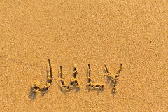 July - word inscription on the gold sand  beach. Royalty Free Stock Photography
