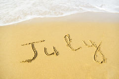 July. Written in sand on beach texture - soft wave of the sea Stock Photos