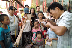 On July 31, 2014 in xi 'an wild goose pagoda scenic area in the square, a folk artists intently rub blowing the calf, lamb, small Royalty Free Stock Photo