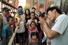On July 31, 2014 in xi 'an wild goose pagoda scenic area in the square, a folk artists intently rub blowing the calf, lamb, small Royalty Free Stock Photos