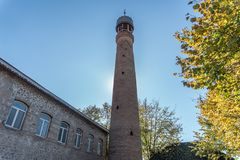 Juma Mosque minaret against solid blue skey. Trees with autumn leaves stock image