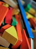 Children`s Wooden Building Blocks Brightly Colored in Toy Box. A jumble of colorful wooden building blocks in a children`s toy collection stock photo
