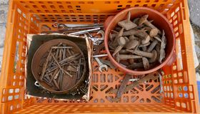 Jumble of old rusty nails and hand tools in a orange plastic box. Jumble of old rusty nails and hand tools. Old rusty messy hand tools in a orange plastic box stock photo