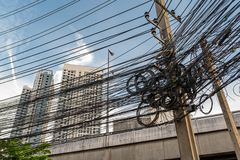 Jumble of overhead electricity and communication cables. In Thailand royalty free stock photography