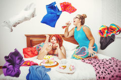 Jumble. Portrait of beautiful plus size curly red hair young women eating sweet pastry in bed Stock Photos