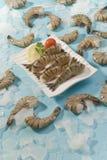 Jumbo headless shrimps with lemon and cherry tomato on white plate royalty free stock photos