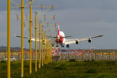 Jumbo jet airliner landing at airport. Jumbo jet airliner about to land on runway, ith landing lights Stock Image
