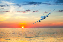 Jumbo jet airplane flying above tropical sea Stock Images