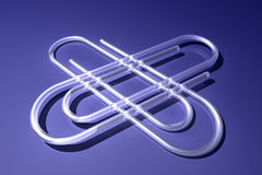 Jumbo paperclips. A pair of jumbo paperclips on blue Stock Image