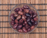 Jumbo pitted kalamata olives. In bowl on bamboo placemat stock images