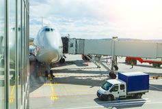 Jumbo Plane Head. Big passenger plane at gate at the airport front view. Sunny cloudy day. Stock Photography