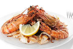 Jumbo prawns and grilled squids with black rice isolated on whit Stock Photo