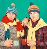 Jumeaux avec les tasses sérieuses de prise de visages Saison et amitié d'automne photos libres de droits