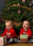 Jumeaux de bébé avec des cadeaux de Noël Photos stock