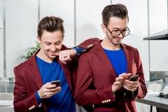 Jumeaux de frères d'affaires avec des téléphones Images libres de droits