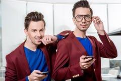 Jumeaux de frères d'affaires avec des téléphones Photographie stock libre de droits