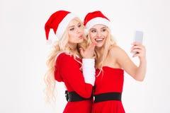 Jumeaux de soeurs envoyant le baiser et faisant le selfie utilisant le téléphone portable Images stock