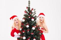 Jumeaux de soeurs se cachant derrière l'arbre de Noël Photographie stock