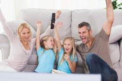 Jumeaux et parents soulevant des bras tout en regardant la télévision Images stock