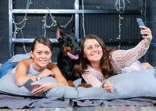 Jumeaux faisant le selfie dans le lit avec le grand chien Image stock
