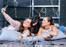 Jumeaux faisant le selfie dans le lit avec le grand chien Photo stock