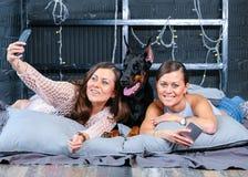 Jumeaux faisant le selfie dans le lit avec le grand chien Photographie stock libre de droits
