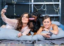 Jumeaux faisant le selfie dans le lit avec le grand chien Photos libres de droits