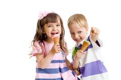 Jumeaux heureux d'enfants avec la crême glacée d'isolement image stock