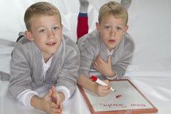 jumeaux identiques de 6 années écrivant la lettre à Sant Image libre de droits