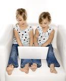 Jumeaux jouant sur l'ordinateur. Image stock