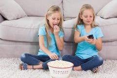 Jumeaux mangeant du maïs éclaté et regardant la télévision Photographie stock