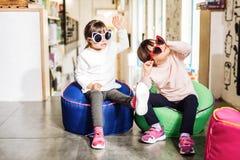 Jumeaux utilisant les espadrilles roses lumineuses et les lunettes de soleil drôles image libre de droits