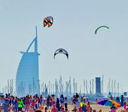 Jumeirah Beach kite day. Jumeirah Beach Dubai kite day with Burj Al Arab in background colorful people following event few kites flying in sky Royalty Free Stock Images