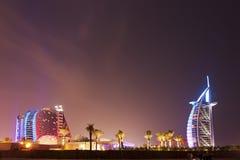 Jumeirah hotell och Burj Al Arab på natten Arkivbild