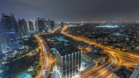 Jumeirah Lake Towers residential district aerial night timelapse near Dubai Marina. Illuminated modern skyscrapers and traffic from above. Villas and houses on stock footage