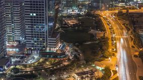 Jumeirah lake towers residential district aerial night timelapse near Dubai Marina. Illuminated modern skyscrapers with park and traffic from above stock footage