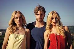 Jumelle des femmes avec le macho sur le fond de ciel bleu Photo libre de droits