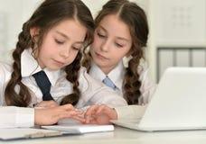 Jumelle des filles à l'aide des dispositifs numériques photographie stock