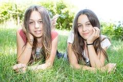 Jumelle des soeurs se trouvant sur le pré vert Photographie stock