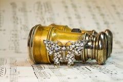 Jumelles antiques de théâtre au-dessus des notes de musique photo stock