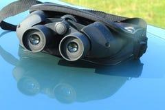 Jumelles dans la poche sur le capot de la voiture. Images stock
