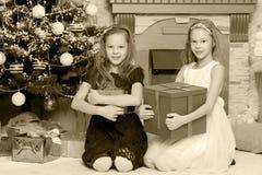 Jumelles de filles avec l'arbre de Noël des cadeaux e Image libre de droits