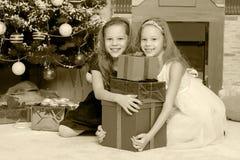 Jumelles de filles avec l'arbre de Noël des cadeaux e Images stock