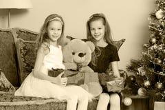 Jumelles de filles avec l'arbre de Noël des cadeaux e Photographie stock