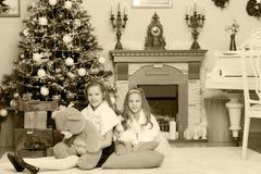 Jumelles de filles avec l'arbre de Noël des cadeaux e Image stock