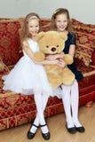 Jumelles de filles avec un ours de nounours Photographie stock