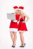 Jumelles de soeurs dans des robes et des chapeaux du père noël avec l'ordinateur portable Photographie stock libre de droits