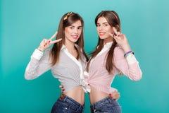 Jumelles de soeurs sur le fond bleu Photos stock