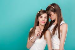 Jumelles de soeurs sur le fond bleu Photographie stock