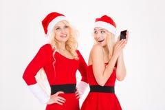 Jumelles espiègles drôles de soeurs dans des robes et des chapeaux du père noël Images libres de droits